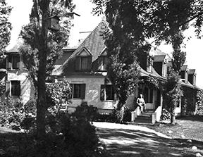 Arthur Amosassis sur la main courante du manoir dans les années 1930. (Collection Héritage canadien du Québec)