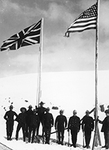 Agents de la Gendarmerie royale du Nord-Ouest à côté des drapeaux américain et britannique (canadien) à White Pass, le long de la frontière entre l'Alaska et le Yukon. (University of Washington : Special Collections, Hogg 540).